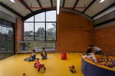 The arched pavilions hold classrooms and play areas. Bright colours, including vibrant shades of blue and yellow, give each room a particular character while also allowing for easy identification. Roof Sheathing, Waiting Area, Red Bricks, Ceiling Windows, Sliding Glass Door, Pavilion, Shades Of Blue, Kindergarten, Architecture