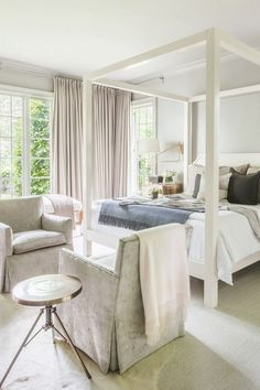 Minimal bedroom with a white canopy bed frame, neutral hues, and velvet accent chairs at the foot of the bed