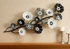 Black & White Wall Vine by Scott Johnson.  Kiln formed art glass is shaped into flowers in cool black and white tones. Each flower is screwed onto the end of the hand sculpted vine made of aluminum. Colors can easily be changed and replaced also making shipping very simple. Each piece is unique.  Find it at www.artfulhome.com