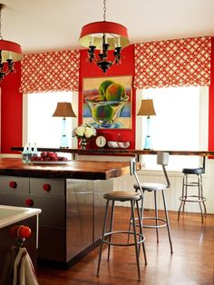Make Over Kitchen Color  Before color was added to this kitchen, it was safe and serviceable but lacked pop. With a fiery red wall and windows accented with patterened roman shades, the room grabs your attention. The color scheme comes full circle with red knobs on the island and matching shades on the pair of chandeliers.
