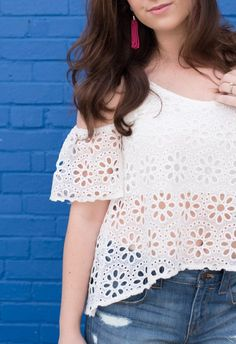 Adorable cold shoulder white top with floral cut outs. Worn with distressed denim shorts and a chunky brown heel. Perfect for a casual summer look.