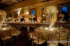 Amber uplights with all white tall centerpieces, gold chivari chairs, votives
