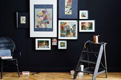 Ansicht einer fertigen Collage an einer Wand. Im Vordergrund sind ÄLMSTA Stuhl aus schwarzem Rattan und FIXA Werkzeugsatz zu sehen.