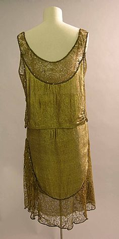 Evening Dress Date Produced:  1924-c1925 Materials:  Silk; Lace; Muslin. This evening dress was worn by Anne Messel. It is made of gold tissue mounted on dark red silk with a bodice of flesh-toned muslin. It has a separate bodice which sits over the dress. The skirt of the dress is overlaid with gilt lace, reinforced with brown lace and studded with small diamanté studs. Metallic fabrics were highly fashionable during the early 1920s as was the straight cut. Back