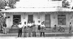 FRANK MORRIS (fourth from left wearing visor) standing in front of his shoe store in Ferriday, Louisiana, c.1950's. | On Dec. 10, 1964, Frank Morris, a 51-year-old, black shoe-shop owner was burned alive inside his store in Ferriday, La. He survived severe burns to all of the skin on his body, was hospitalized and lived four more days before he died. The FBI investigated twice in the 1960's with no conclusion. (Photo courtesy of the Concordia Sentinel and William Brown, 2010…