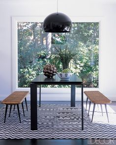 Funny black! | dining room designed by Eric Hughes features a table and suspension lamp by Kartell, 1930s benches, and a carpet by Madeline Weinrib; the sculpture is by Pamela Sunday.