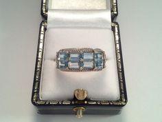 Deze prachtige art deco ring is geel goud en heeft een kop van 2 cm bij 8 mm. Gezet met 8 blauwe  topazen en 2 diamanten.  Gezet met:  Topaas 8 x 5 x 3 mm. Baguette geslepen, blauw Diamant  2 x 1 pt, briljant geslepen, I /SI   Gewicht: 2,80 gr  Ringmaat: 18/56  Keurmerk: SC (meesterteken), weegschaal,  375 d.i. 9 kt goud (in NL bwgg), leeuw.  De ring kan eenvoudig op maat gemaakt worden. Verzending: aangetekend pakket