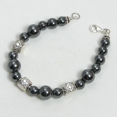 "Handmade gemstone hematite bracelet features a strand of semi-precious hematite gemstones, sterling silver southwest accent beads, wire band, and lobster claw clasp. 7"" in length. Add a necklace, pend"