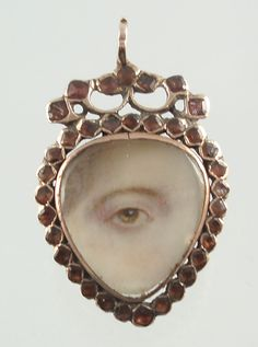 Lover's eye miniature pendant - Georgian C. 1790 -   Expressive brown female eye miniature, watercolor on ivory, set in a modified heart motif surrounded by garnets.
