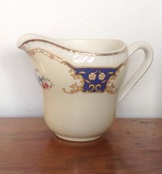 An elegant cream or milk jug made by Portland Pottery in the 1940s/50s. Cream with gold edging and alternating blue/gold and pink floral pattern.  Base is stamped.. RIDGWAY PORTLAND POTTERY COBRIDGE. EST 1792. STAFFORDSHIRE ENGLAND. Jug measures 5.4 handle to spout, 3.3 diameter and 3.5 tall. It holds 10oz ( 1/2 pint ) of liquid.  There is slight wear to the gold edging around the spout, otherwise I good vintage condition, with no chips or cracks. A very pretty piece to enhance your vintage…