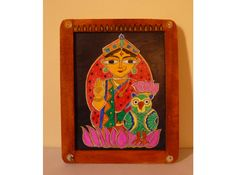 Here's an unconventional image of Goddess Lakshmi and her vahana, the owl on a stone slate with a wooden frame. Welcome and pray to the Goddess of Wealth, Lakshmi this Diwali with this bright hand painted image which is rustic as well as stylish.