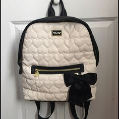 Black and white Betsy Johnson backpack! Heart quilted black and white Betsy Johnson backpack! Super cute, plenty of room for notebooks, folders, and a book or two. Adorable silky pink flower inside! Consists of 2 pockets. There is a small pen mark on the outside as pictured. Open to offers :) Betsey Johnson Bags Backpacks