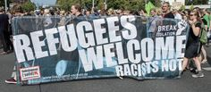 Protesters demonstrate with a banner saying 'Refugees welcome' in Dresden, eastern Germany, on Saturday 29 August