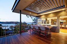 Warm contemporary patio design of bayview house by applying wooden chairs and table served with romantic bay scenery