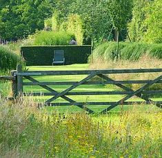 I love the contrast between the rough grass and farm gate and the neat severity of the garden beyond (apart from the grasses on the right).