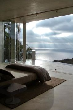 Open bedroom to magnificent view of ocean bay as sun rays break through clouds.