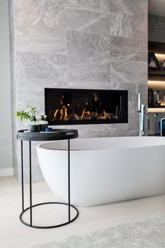 Cosy yet contemporary bathroom design with a spot to put a drink and a book whilst you bathe and enjoy the extra warmth on cooler days from the fire. Interior design and imagery courtesy of interior designers Stephenson Wright Bathroom Fireplace, Tiled Fireplace Wall, Mobile Home Makeovers, Kitchen Makeovers, Bathroom Makeovers, Contemporary Bathroom Designs, Contemporary Design, Dream Bathrooms, White Bathrooms