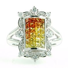 Calibre-cut Sapphires ranging in color from Burnt Orange to very light Yellow create a plaque of color which is surrounded by colorless diamonds in this contemporary ring.