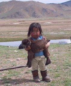 Little Mongolian girl holding a goat baby