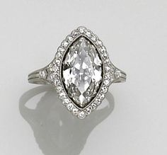 A diamond and platinum ring, circa 1900  centering a marquise-cut diamond within a six-prong setting surrounded by single-cut diamonds, shoulders accented by old European-cut diamonds; estimated center diamond weight: 1.80 carats; estimated total diamond weight: 2.25 carats.