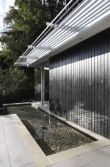 Superb architect designed house: the modern kitchen and living area open out via a glazed sliding wall onto the large patio and surrounding garden. South east London.