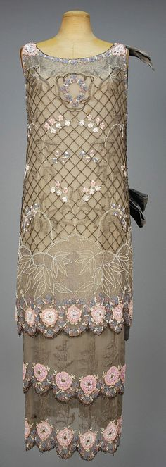 Circa 1920 Beaded Chiffon Dinner Dress: Two piece grey silk having sleeveless tunic and under dress decorated with a pastel floral on a lattice of black iridill beads, two-tiered under dress all with scalloped hem bands.