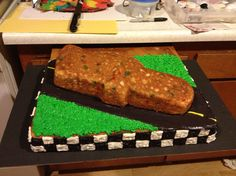 I started with a half sheet cake and decorated the checkered flag, road and grass. Then I baked a funfetti cake with a cars shaped pan
