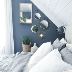 White and steel blue combine for a surprisingly light and airy Nordic style bedroom. The mirrors add interest to an award section of wall space while also creating the feeling of more space. Attic Bedroom Designs, Bedroom Loft, Blue Bedroom, Dream Bedroom, Master Bedroom, Bedroom Decor, Slanted Ceiling Bedroom, Slanted Walls, Modern Home Interior Design