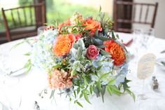"""These orange roses are """"Free Spirit"""" Roses. I love them in combination with the blues and white hydrangeas, blue thistle(?), and light pink """"Spray Roses""""."""