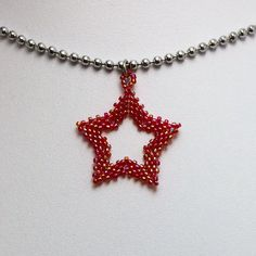 Beaded star pendant made with red sparkling beads! Measures approximately 28x28mm. Comes on a 14 or 16 inch length of ball chain. Hand beaded using Matsuno glass seed beads, fireline thread, and chrome ball chain. * Cat allergy? I have two cats, who roam where I bead! * If you would like a different colour variation, or you have any other questions or comments, please just ask :) Klouwaldron@gmail.com www.etsy.com/uk/shop/GoodBeadDeeds