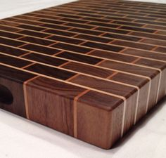 This here is a end grain cutting board made in a brick wall pattern. Entire cutting surface is 100% end grain including grout joints. Woods used are Walnut as the bricks, Cherry and Hard Maple as grout joints. Board measures 12 inches wide 18 inches long and 1.5 inches thick. End grain cutting boards are very durable and are engineered for many years of use. End grain is better for knives staying sharp much longer than long grain wood cutting boards. Recessed finger holds are routered into…