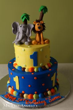 Baby Animals #21Animals  This cake is made up of two tiers that are iced smoothly in colored buttercream with mini polka dots surrounding. The animals are handmade from gum paste, along with the palm trees. They make a great topper for any celebration. The colors can be changed to match your event.