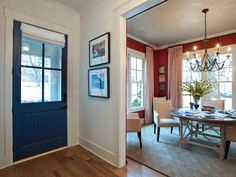 A navy blue front door makes a colorful welcome in this home's foyer, especially when paired with the red walls of the adjacent dining room. A Roman shade lets down over the door's windows for more privacy. Grey Front Doors, Front Door Colors, Front Entry, Front Porch, Furniture Layout, Living Room Furniture, Dining Rooms, Foyer Furniture, Hgtv Dream Homes