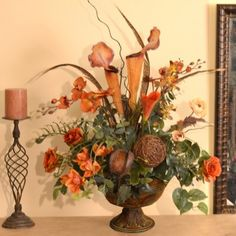 "Rust Orchids Pitcher Plant and Feather Faux Floral Arrangement AR361 - Bring color and warmth to your home with our designer quality rust orchid and pitcher plant silk floral arrangement. Created in a metal pedestal vase with feathers, grasses, roses, calla lily, vine sphere, natural pods and willow. This natural looking silk floral design can be customized to match your homes decor, color and size. Measures 27""H x 20"" W x 14""D"