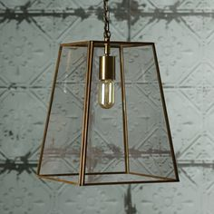Simple glass pendant with sloped sides, all framed in gently antiqued brasswork. The height of elegance