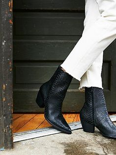 luxe leather ankle boot features a pointed toe and a stacked heel.