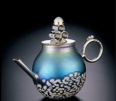 "Mabe Teapot Blown glass vessel adorned with sterling silver, 22 karat gold and pearls. Metal is constructed, soldered and polished. Spout and handle are bolted through the glass. Lid is domed and decorated with gold spheres and mabe pearl sitting atop a pyramid of silver rings. 6"" tall"