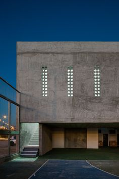 Exposed concrete school extension designed to keep out stray balls from the adjacent sports court