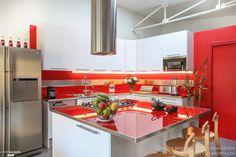 Une cuisine moderne de type industriel avec couleur forte orange. Béton, verre, métal et bois ont été utilisés.