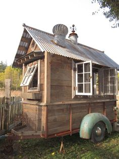 Just plain cool. Rustic old wooden shed with tin roof on trailer with wheels.