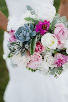 Pink, white, and green bouquet of roses, lisianthus, and succulents.