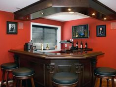 The punch of deep red on the walls gives an impression of luxury and sophistication, especially when combined with a dark wood bar and matching stools.