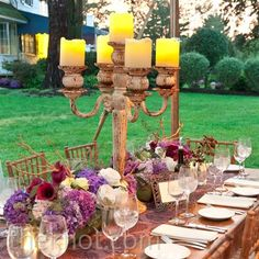Create a warm outdoor table setting, with an eclectic mix of items; giant aged candelabras, fabric runners, and low, lush arrangements.