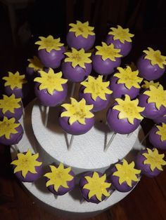 Here are some Tangled (Rapunzel) inspired cake pops for my Daughters 5th birthday. She took these to school. They are Chocolate mud with Chocolate buttercream and covered in Orchid Candy. The Sunflowers are made using fondant and edible glitter.