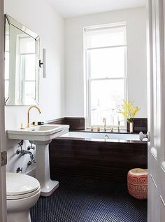 Stunning black and white monochromatic bathroom with built-in marble bathroom and bright brass gold fixtures on the sink and tub. Read more about Julia Chaplin's gypset brownstone and see the full tour on our Style Guide!
