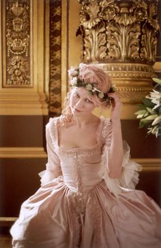 Kirsten Dunst as the Queen of France wearing a pink taffeta dress with ruffles and tulle embellishments and sporting cotton candy pink hair.