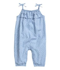 Jumpsuit in woven cotton fabric with a printed pattern. Elastication and ruffles at top, elasticized shoulder straps with decorative bow, snap fasteners at insides of legs, and elasticized hems.
