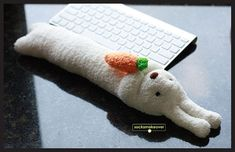 A creamy white bunny keyboard wrist rest with safety eyes and nose, holding a carrot, 17 inches long $19.95