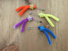 """Shooting star swaps! By Troop 10437, Louisiana East. Fold a 3"""" pipe cleaner in half, insert through circle at end of safety pin. Slide star bead over both sides of pipe cleaner. Twist pipe cleaner together 1-2 times, curve slightly. Great inexpensive swap that's simple for younger girls."""