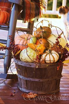 Rustic Fall/Thanksgiving decor- big basket filled with pumpkins, squash, gourds, berries & wispy grapevines.
